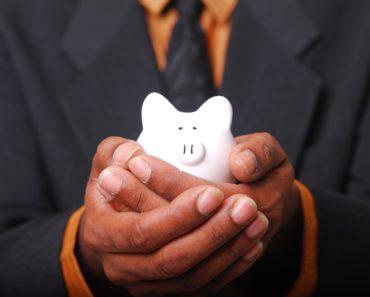 Holding a small piggy bank