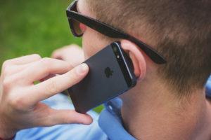 A man using an iPhone to make a call