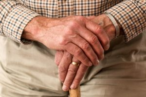 An elderly person clasping his hands
