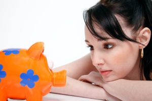 Young woman looking at a piggy bank