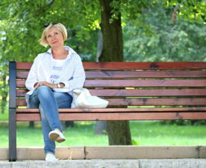 An older lady happily sitting on a park bench