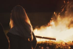 A girl stands close to a bonfire