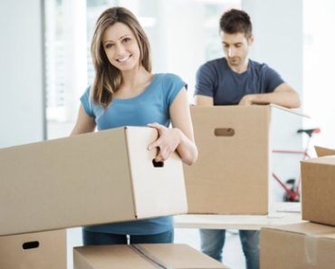 Young couple pack boxes during house move