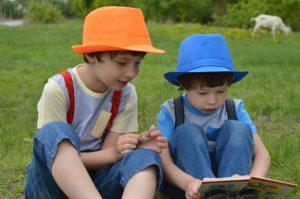 Children enjoying a book in a field