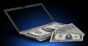 Dollar bills and a laptop
