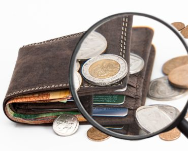 Looking at a wallet and cash through a magnifying glass