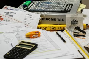 A calculator, bills and a tax return