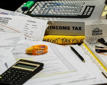 A calculator, bills and a tax return