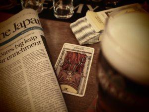 A tarot card and a newspaper