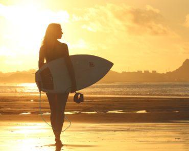A woman surfer on a sunny beach