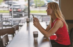 A young woman using her smartphone in a cafe