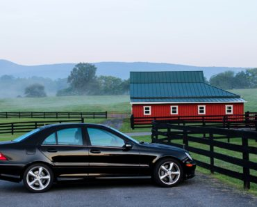 A car parked in front of a picturesque barn barn