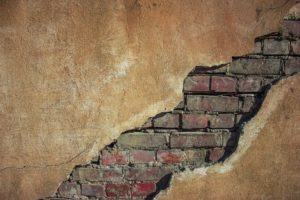 An old brick wall with cracked plaster